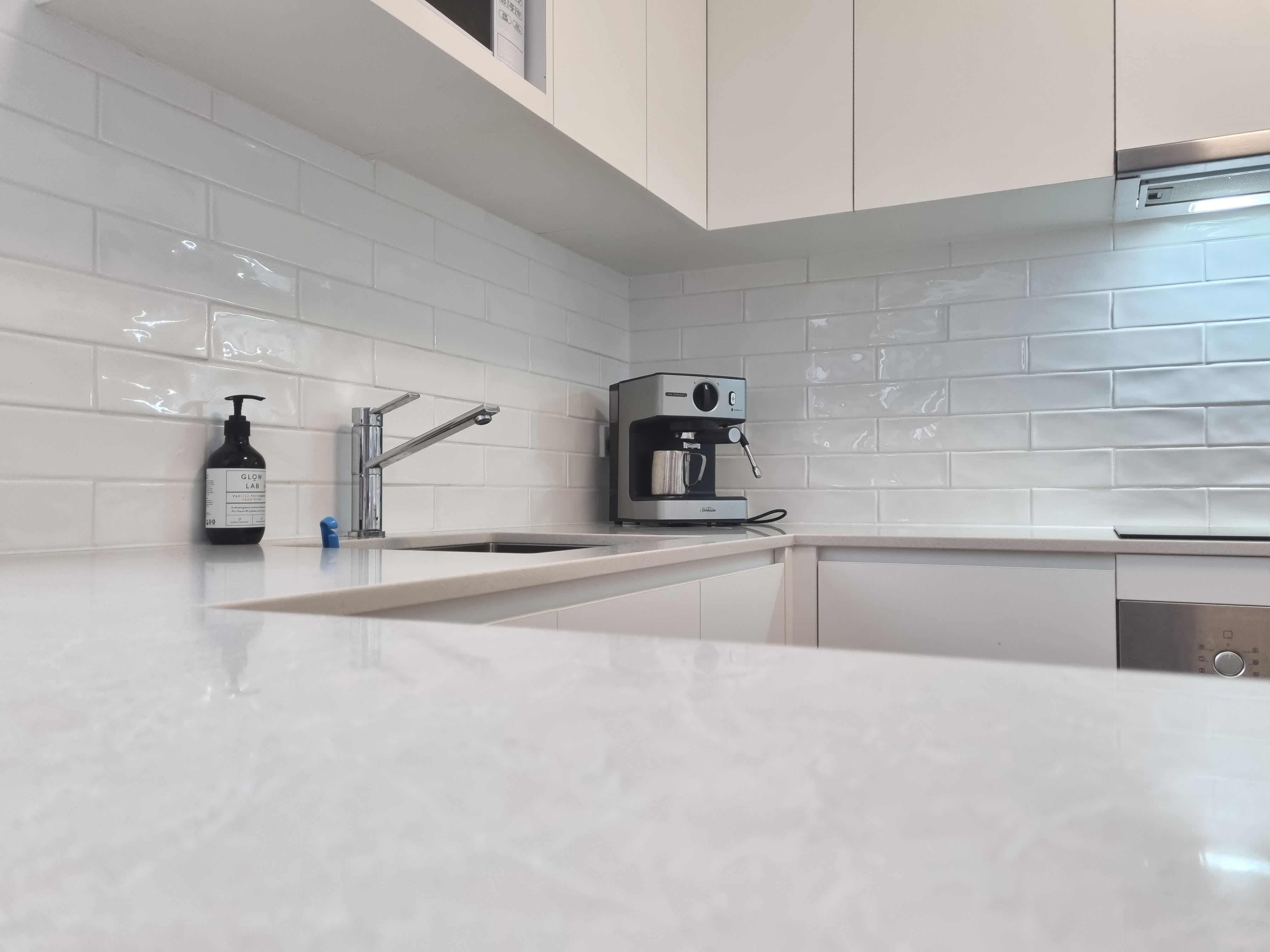 BrisbaneKitchenDesign St Lucia Contemporary Kitchen Laminate Flat Panel Doors with Caesarstone Cosmopolitan White Benchtops and Integrated Handles